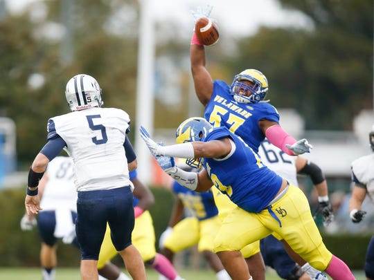 Delaware defensive lineman Grant Roberts knocks down a pass by New Hampshire quarterback Sean Goldrich as Hen Blaine Woodson pressures in the second quarter at Delaware Stadium in a 2015 game.