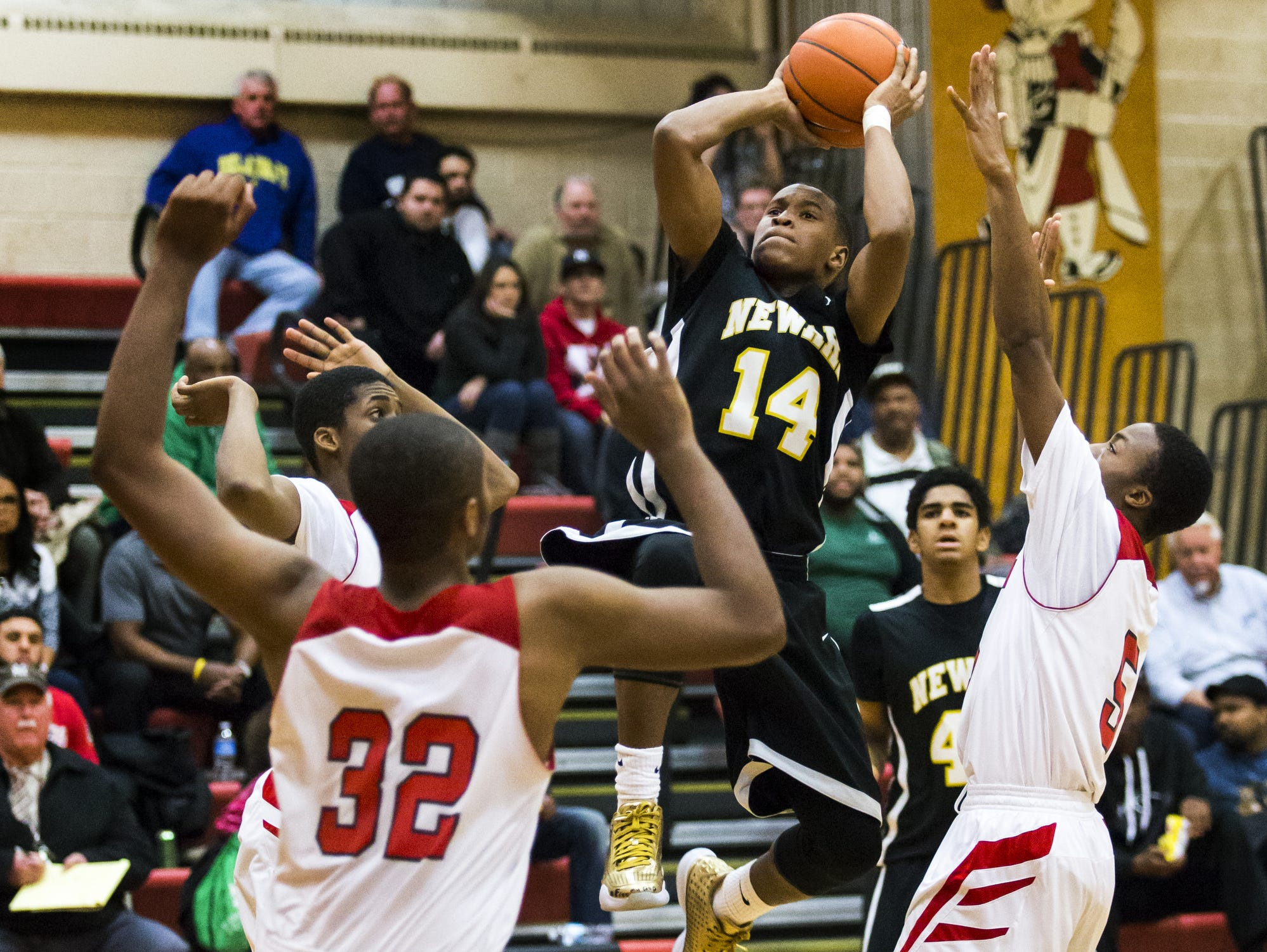 Newark's Michael Drumgo-Sharpe puts up a shot through a group of William Penn defenders in the second half of William Penn's 47-28 win over Newark at William Penn High School on Thursday night.