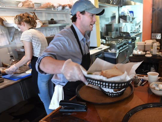 Jeff Bowers, center, owner of the New Hudson Cafe works on getting sandwiches out to customers on July 17. The restaurant is at 56849 Grand River Ave. in New Hudson.