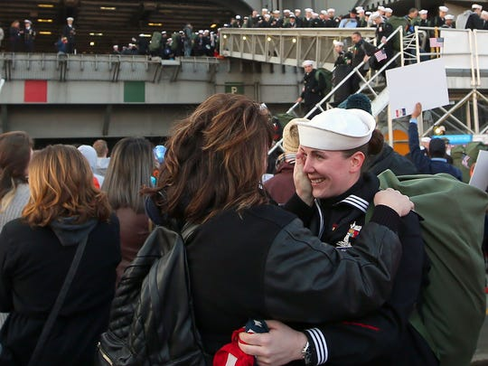 Jennifer Misgen (left) embraces her daughter Elizabeth Hockensmith, a sailor aboard the USS Nimitz, at Naval Base Kitsap-Bremerton on Sunday, December 10, 2017.