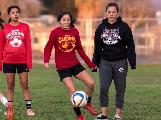 Orosi coach Sara Carter, right, watches Orosi's Victoria Quevedo and teammates practice Monday, February 12, 2018.