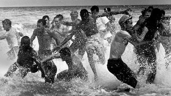 """Mob attacks protesters wading into water at """"whites-only"""" Biloxi Beach on April 24, 1960."""