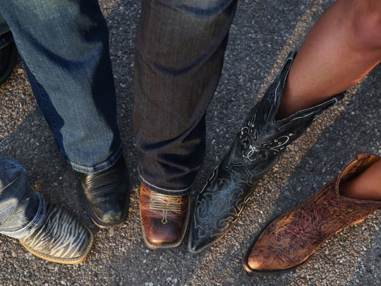 A group of women show off their boots before the Dierks Bentley concert at the Iowa State Fair grand stand on Monday, Aug. 15, 2016, in Des Moines.