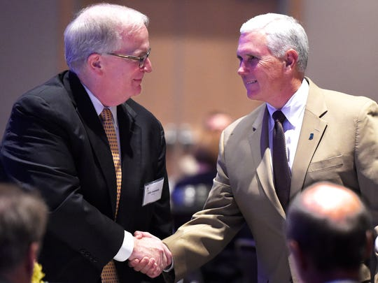 Gov. Mike Pence (right) greets Carl Chapman, Vectren Chairman, President and  CEO, before speaking at the Southwest Indiana Chamber luncheon Wednesday announcing that Indiana will not comply with an impending federal plan to reduce carbon emissions from power plants, June 24, 2015.