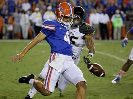 Florida punter Kyle Christy (4) manages to punt the
