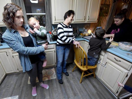 Krista Kouneski, left, holds her son while she, her