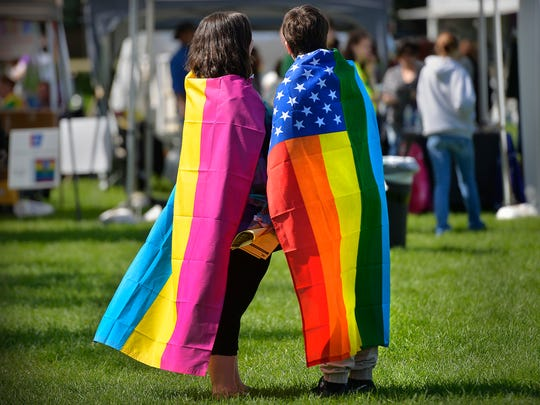 Couple Nikki Sloan, left, and Kimmy Luke of St. Cloud wear flags in support of the St. Cloud Pride celebration during the 2015 Pride in the Park event. This year's Pride in the Park marks 9 years of the annual event.