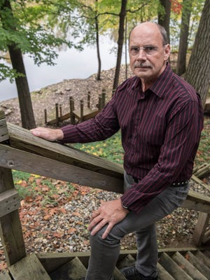 Randy Vallance stands on stairs in his backyard that lead to the Kalamazoo River. The Emmett Township resident moved into his South Shore Drive home about three years ago, unaware of long-known unsafe arsenic levels in his water well.