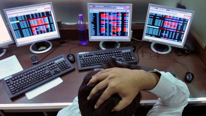 An Indian stockbroker reacts as he watches share prices on his computer during intraday trade at a brokerage firm in Mumbai on August 3, 2011. Indian shares slid as much as 1.23 percent and below the 18,000-point level in early trade August 3, tracking regional markets on concerns of a weakening global outlook. The benchmark 30-share Sensex index on the Bombay Stock Exchange fell 223.32 points to a day's low of 17,886.57, before recovering marginally to 17,943.47 but still down 0.92 percent. AFP PHOTO/Indranil MUKHERJEE (Photo credit should read INDRANIL MUKHERJEE/AFP/Getty Images) ORIG FILE ID: Del493403