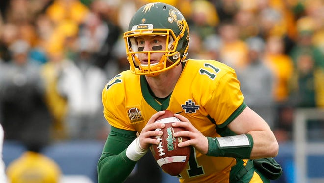 North Dakota State Bison quarterback Carson Wentz (11) rolls out against the Jacksonville State Gamecocks in the first quarter in the FCS Championship college football game at Toyota Stadium.