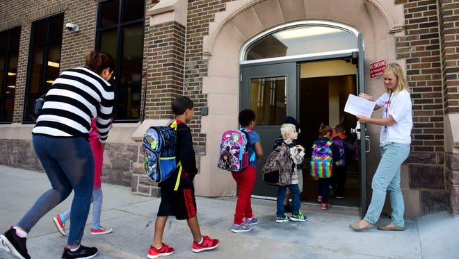 Students are led into the building by a teacher before the first day of school at Lowell Elementary. All Sioux Falls public schools opened their doors Tuesday for the first day of school.