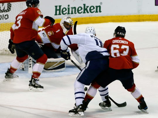 Toronto Maple Leafs center Zach Hyman (11) takes aim at the puck as he scores his second period goal under pressure from Florida Panthers right wing Evgenii Dadonov (63) in an NHL hockey game, Tuesday, Feb. 27, 2018, in Sunrise, Fla. (AP Photo/Joe Skipper)