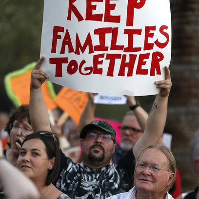 """Jimmy Gretillat holds a """"Keep Families Together"""" sign"""