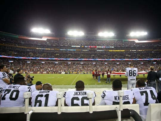 Oakland Raiders players sit on the bench during the national anthem prior to the game against the Washington Redskins at FedEx Field.