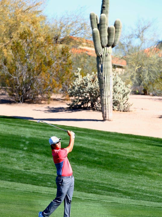Byeong Hun An, of South Korea, hits his approach shot into the second green during the third round of the Waste Management Phoenix Open golf tournament Saturday, Feb. 4, 2017, in Scottsdale, Ariz. (AP Photo/Ross D. Franklin)