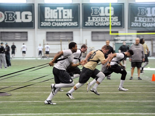 Michigan State linebackers pull against a resistance system during team conditioning in East Lansing on March 3, 2015.