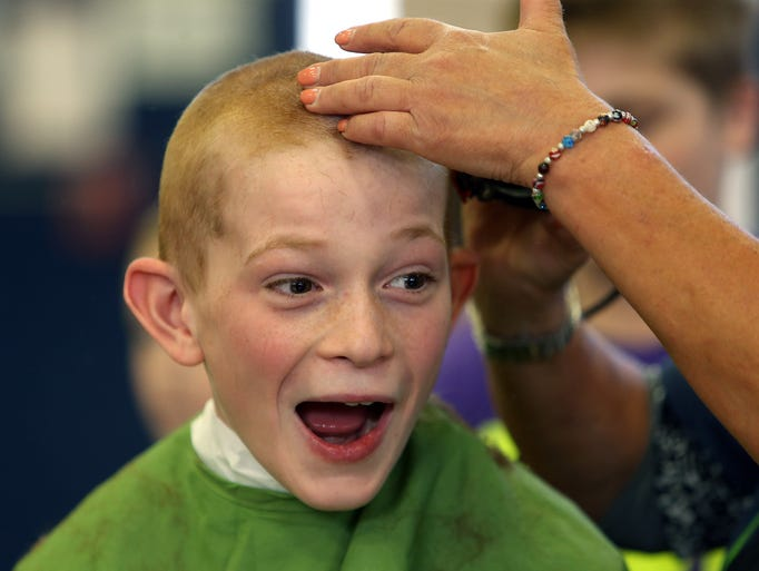 Ryan Donnelly reacts as he get his head shaved  as