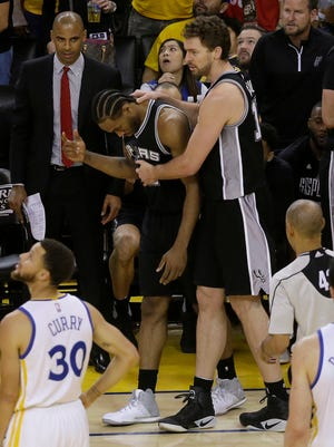 San Antonio Spurs forward Kawhi Leonard, center left, gestures next to center Pau Gasol during the second half of Game 1 of the NBA basketball Western Conference finals against the Golden State Warriors.