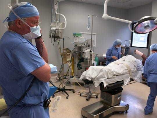 """Dr. Andy Moore, left, dictated information about the hand surgery he had just performed as part of the Surgery on Sunday program. Moore, the program's founder, said providing the services in Lexington """"is just pure joy."""""""