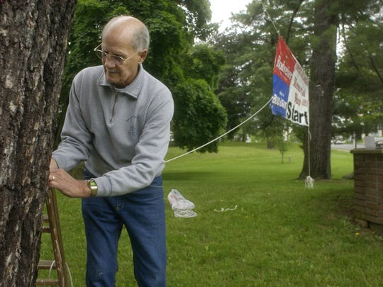 In this June 2006 file photo, Pete Sanfilippo hangs a banner for the Joseph McDonald/Bill Crusie Memorial Run in Messier Park in the Village of Wappingers Falls.