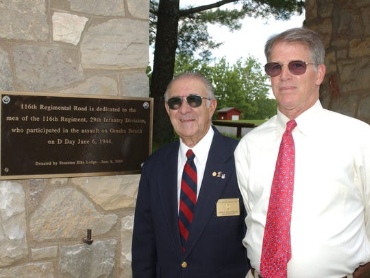 Jim Cacciapaglia, left, and Ned Bonfoey pose beside the plaque memorializing the efforts of the 29th Infantry on the 116th Regiment National Guard Unit in 1999.