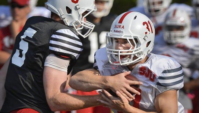 St. John's University senior running back Sam Sura (31) takes the handoff from senior quarterback Nick Martin (5) during practice Wednesday at Clemens Stadium.
