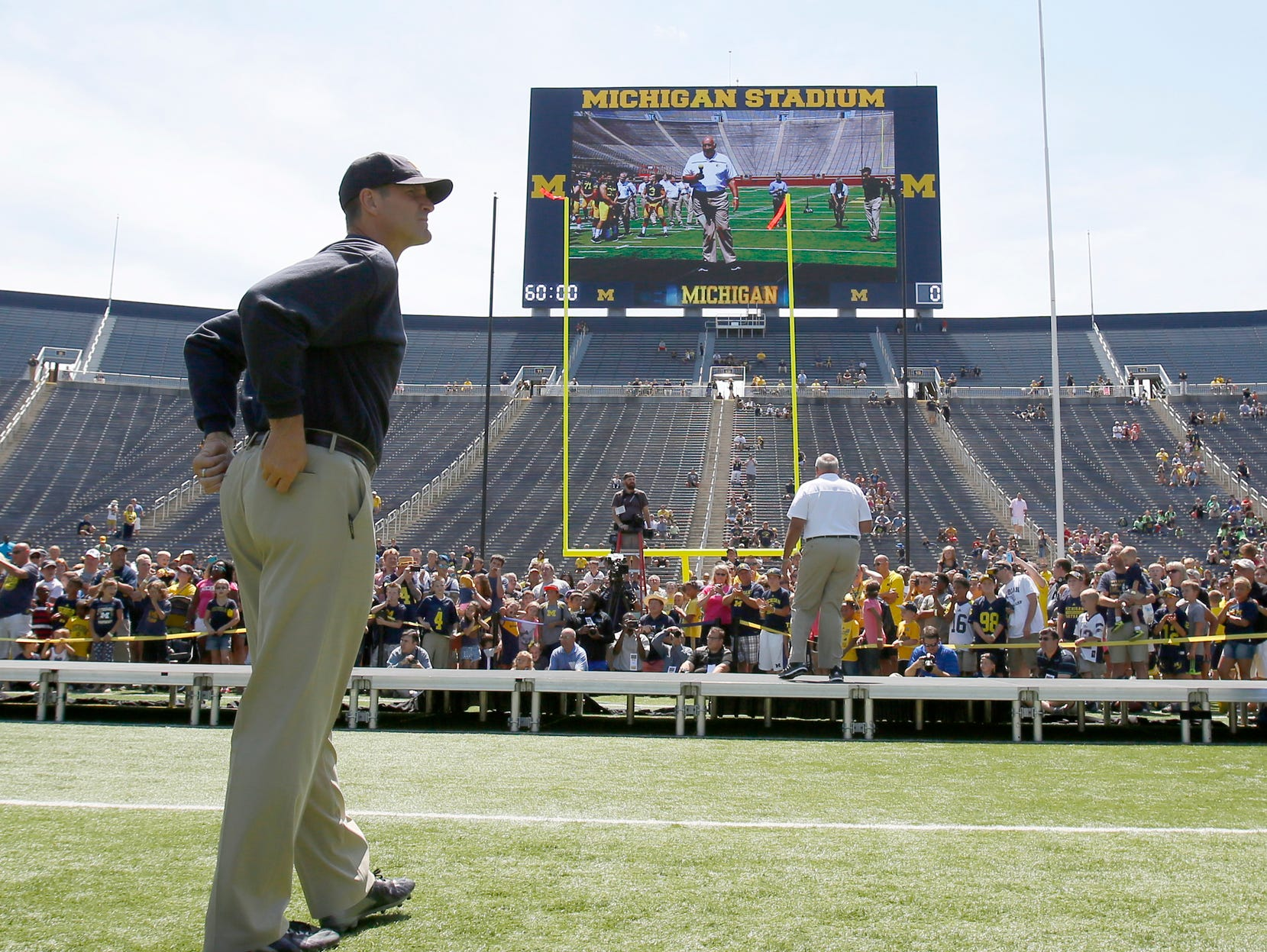 Michigan head coach Jim Harbaugh oversees the introduction of the team's players by position group at media day August 6, 2015, in Ann Arbor.