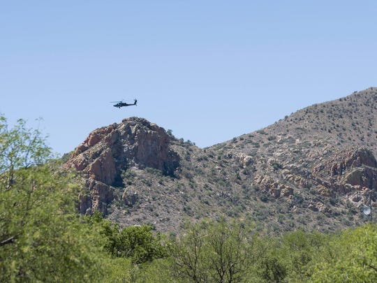A military helicopter hovers near the border. Neither