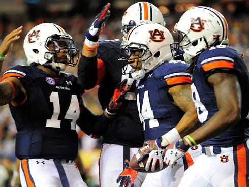 Auburn Tigers running back Cameron Artis-Payne (44) celebrates a touchdown with quarterback Nick Marshall (14) during the fourth quarter of the 2013 SEC Championship game against the Missouri Tigers at Georgia Dome.