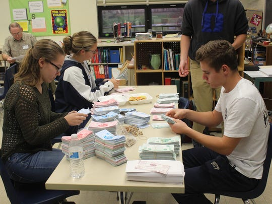 Elco High School Interact Club members, from left, Kayla Light, Alyssa Keath and Evan Gettler count coupons that will be distributed to needy families in the Elco School District, who can exchange them for free turkeys at a local grocery store.