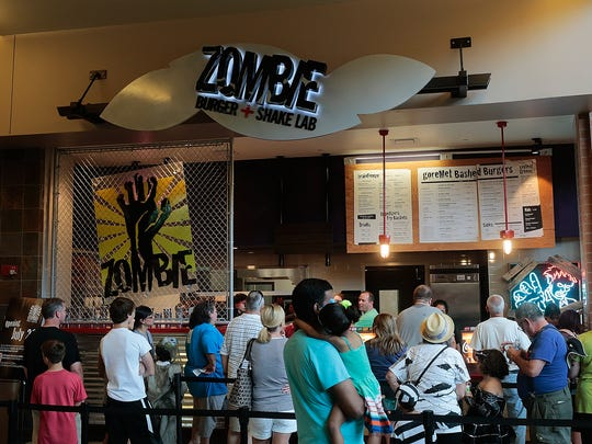 Customers wait in line to order at the opening of Zombie
