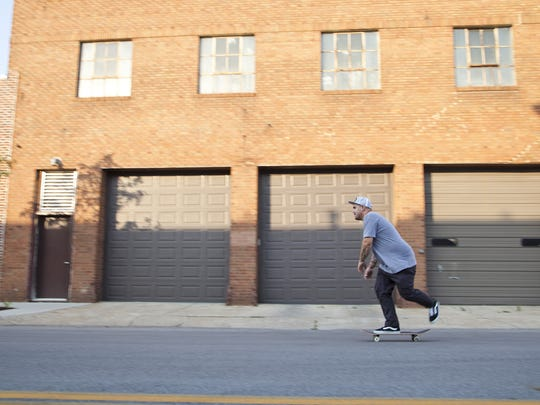 Subsect Skate Shop manager Kevin Jones, 34, cruses down East Third Street in 2012.
