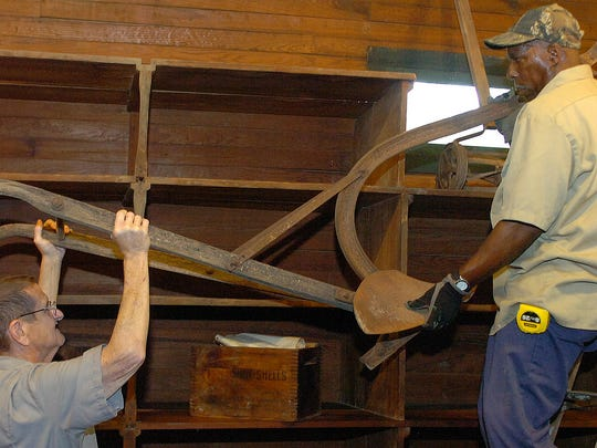 Elmer White, left, and Howard George hoist an antique plow onto a shelf in the Emar Andrepont General Store located at Le Vieux Village. Opelousas Tourism was recently awarded $3,000 in state grant funding for a General Store Exhibit to enhance tourism and preservation efforts for the Andrepont store and Le Vieux Village.