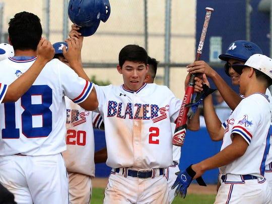 Matt Holguin, 2, of Americas is greeted by teammates in the dugout after scoring a run against Coronado on Friday at Americas High School.