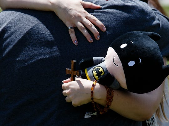 A cross and a stuffed Batman character are held by Jennifer Leonhard as she embraces a supporter after the funeral for her son William Leonhard on Saturday, July 16, 2016 in Des Moines. He was stillborn to his parents who wanted the cosplay community to come and help them celebrate.
