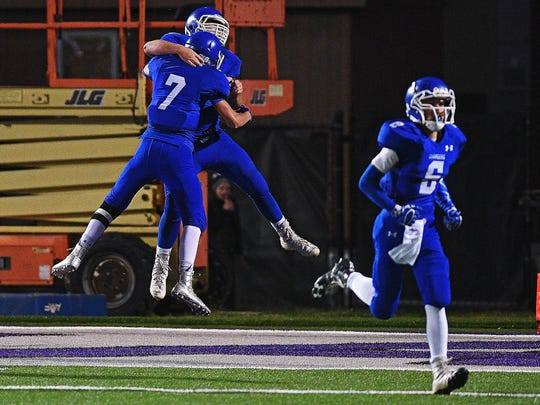 Sioux Falls Christian's Tannen Reu (7) and teammate Isaac Bonnema (76) react after Reu scored a touchdown during a game against Madison Friday, Sept. 30, 2016, at Bob Young Field in Sioux Falls.