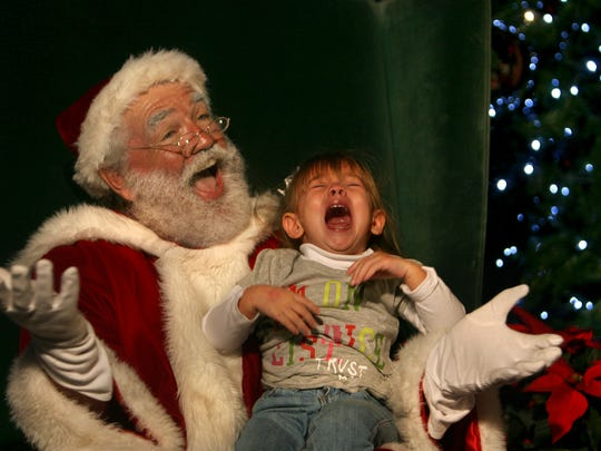Two-year-old Elianna Castro cries while Santa, aka Paul Gagnon, shrugs his shoulders and throws up his hands at the Comcast Holiday Festival of Lights and tree-lighting ceremony, sponsored by The Chamber of Commerce of Cape Coral Saturday, December 3.