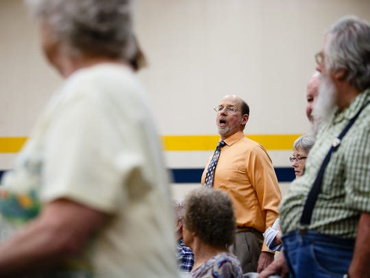 """People sing, """"We shall overcome"""" before Rep. Rod Blum, who represents Iowa's 1st congressional district, appears to answers questions from people during a town hall at Marshalltown Community College on Thursday, May 11, 2017, in Marshalltown."""