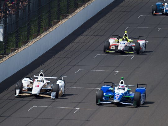 Takuma Sato (26) maintains the lead over Helio Castroneves (3) heading into the final laps of the running of the 101st Indianapolis 500.