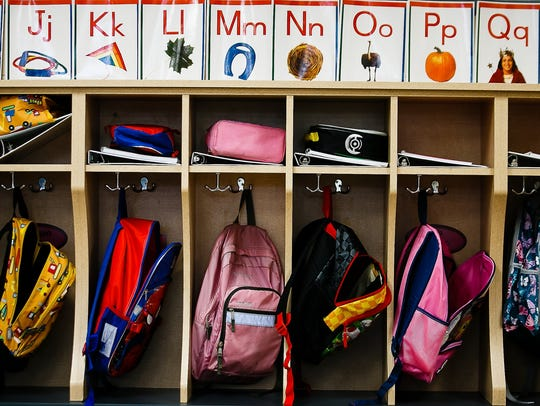 Backpacks hang in cubbies on the first day of school