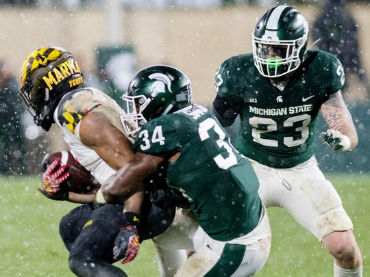 Michigan State's Antjuan Simmons, center, and Chris Frey, right, tackle Maryland's Jermaine Carter, Jr. during the fourth quarter on Saturday, November 18, 2017, at Spartan Stadium in East Lansing.