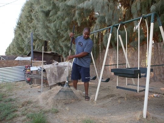 Christopher Williams rakes the needles of the tamarisk trees that dominate his backyard and other homes in the Crossley Tract neighborhood of Palm Springs, Calif. The trees form a physical barrier between the historically black neighborhood and the Tahquitz Creek Golf Course.