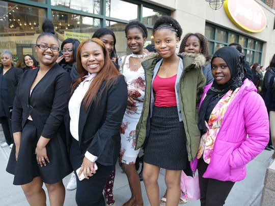 A group of young women pose for photos, before entering