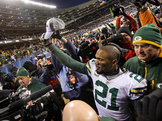 Packers cornerback Charles Woodson holds up an NFC