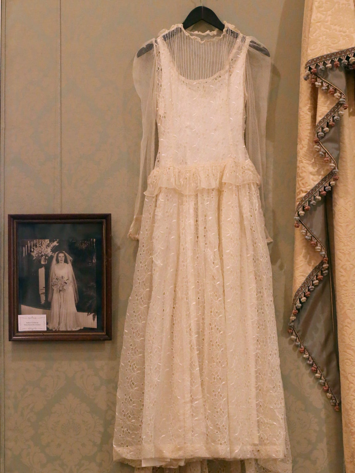 The late Doris Reynolds Crocker wore a handmade dress to her wedding. She is the mother of Oaklands Association treasurer Mark Crocker. The gown is featured in the 'Wedding Dresses Through the Decades' exhibit.