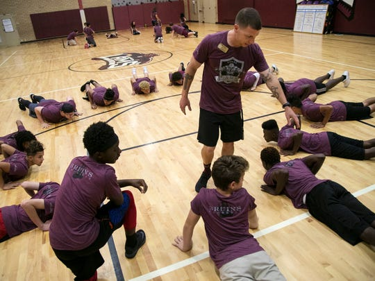 Lehigh Acres Middle School PE teacher Nicholas Ayers works with his CrossFit group on pushup technique before their workout on Friday, October 20, 2017, in Lehigh Acres.