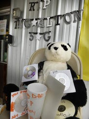 "A bear, CD's and sign reading ""RIP Big Alton"" rest"