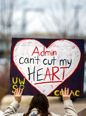 A student holds up a sign during the March for the Arts and Humanities to protest against a proposal to cut 13 liberal arts majors at the University of Wisconsin-Stevens Point, April 12, 2018.