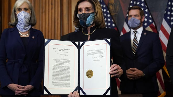House Speaker Nancy Pelosi, D-Calif., displays the signed article of impeachment against President Donald Trump in a ceremony Wednesday before transmission to the Senate for trial on Capitol Hill in Washington.