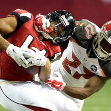 Wide receiver Eric Weems #14 of the Atlanta Falcons is tackled by cornerback Johnthan Banks #27 of the Tampa Bay Buccaneers during a game at the Georgia Dome on September 18, 2014 in Atlanta, Georgia.